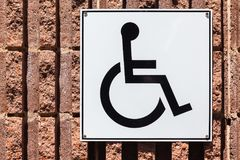 Parking Handicap Disabled Sign Closeup. Parking bay handicap disabled wheel chair sign on textured brick wall for designated vehicles Royalty Free Stock Photo