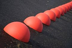 Parking limiters - red concrete hemispheres on asphalt. stock images