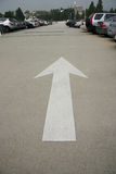 Parking Lot Arrow. White arrow symbol in a parking lot, looking down between the row of cars Stock Photos