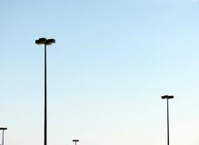 Parking Lot Lighting. Light standards in a parking lot against a clear, blue sky royalty free stock photography