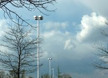 Parking Lot Lighting. A line of light standards in a parking lot on a cloudy, early Spring day royalty free stock photos