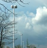 Parking Lot Lighting. A row of light standards in a parking lot on a cloudy, early Spring day royalty free stock photo