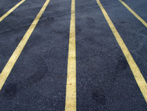 Parking Lot Lines. A strange view of 5 yellow parking lot lines over a cracked asphalt surface with tire marks in the asphalt Stock Photos