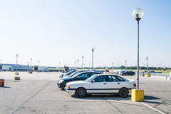 Parking lot of a mall with five cars in the middle of the day. Blue sky, nice weather, lamp Royalty Free Stock Photo