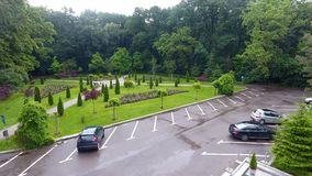 Parking lot in the park after the rain. Parking lot in the forest, green grass and green trees royalty free stock photos