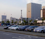 Parking lot with tall modern buildings background. A row of cars parked in parking lot with tall modern office buildings background in Suzhou China stock images