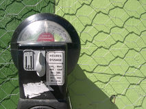Parking meter 1. Parking meter set against a green backdrop and chickenwire fence Stock Images
