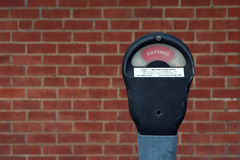 Parking meter. An expired parking meter with brick wall background Stock Photography