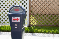 Parking Meter Expired in Front of Fence. Grey parking meter shows an arrow to the space it represents Royalty Free Stock Image