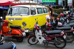 Parking motocycle. Chiang Mai Thailand September, 06-2015: a vintage car parked beside motocycles Royalty Free Stock Photos