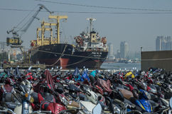 The parking of motorbikes near river, with cargo ships Stock Photography