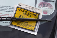 Parking penalty notice. London, UK - May 16th, 2013: A parking penalty notice, under a windscreen wiper on a vehicle. These charges are given when somebody parks Stock Photos