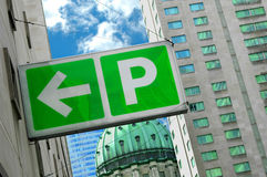 Parking sign in downtown. A green and white parking sign in a downtown area stock image