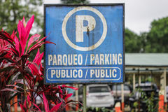Parking sign in latin and english language. Blue color and giant P letter informs about possibility to stay with a car. Public packing, Paqueo publico Royalty Free Stock Image