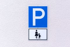 Parking sign for mothers with young children. On a textured white exterior wall Stock Photos