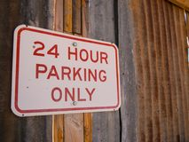Parking sign on rustic wall. 24 hour only parking sign on rustic metal and wood wall Stock Photos