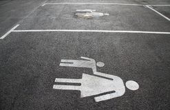 """Parking space for mothers and children. Sign on asphalt """"Mother and child"""". Sign on the street """"Mom and kid"""". Pedestrian s. Ign on royalty free stock images"""