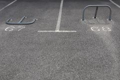 Parking spaces with barriers. Open and closed barriers on numbered parking spaces 67 68 Royalty Free Stock Photography