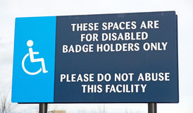 Parking spaces and request about abuse. An image of a disability symbol together with a text message requesting non badge holders not to use the parking spaces stock photography