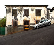 Parking on a steep street. A car parking on a steep hill in front of an old house. The door cannot even be opened due to the steepness of the road. Shot in royalty free stock photography