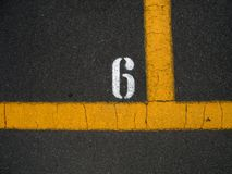 PARKING STRIPES. Parking Space number six. Outlined by Colorized Yellow Stripes Stock Photo