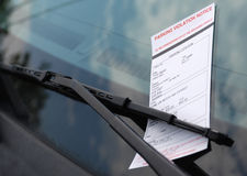 Parking Ticket. A parking violation notice tucked under the windshield wiper blade of a parked vehicle Royalty Free Stock Photos