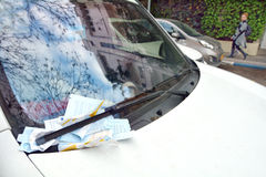 Parking ticket placed under windshield wiper of a car Stock Images