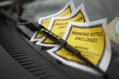 Parking Tickets Under Windshield Wiper. Closeup of parking tickets under windshield wiper of a car Stock Image