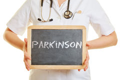 Parkinson written on a blackboard. Holded by a doctor Stock Photos