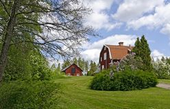 Parklandschaft mit roten Holzhäusern Stockbild