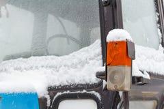 Parklicht und Blinkerlicht wird mit Schnee auf einer alten Traktornahaufnahme umfasst Lizenzfreie Stockfotografie