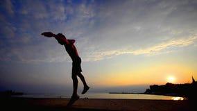 Parkour, garçon de l'adolescence de silhouette de coucher du soleil renverse en ciel, mouvement lent clips vidéos