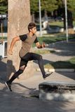 Parkour is for strong. A teenage boy goes in for parkour in a city park stock images