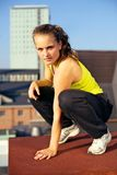 Parkour On Urban Building Rooftop. Balancing on the edge of a high urban industrial building rooftop a female traceur poses for the camera Stock Images
