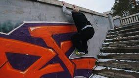 Parkour urbano de la ciudad - cámara lenta que salta - atleta que realiza el libre-funcionamiento en parque del invierno metrajes