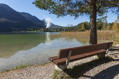 Parkowa ławka na Weissensee z dymem obraz stock