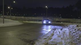 An Parkplatz auf der leeren schneebedeckten Straße nachts mit seinen Scheinwerfern t?tigkeit Einsames Auto mit den Neonscheinwerf stock video footage