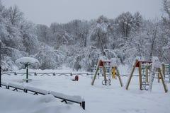Parkspeelplaats met verse witte sneeuw na blizzard in de winter wordt behandeld die Royalty-vrije Stock Afbeeldingen