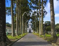 Parkway with small white and gray church of Sao Nicolau at the village of Sete Cidades on the island of Sao Miguel. Azores, Portugal royalty free stock images