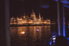 Parlament av Budapest på natten exponerad från Danubet River arkivfoton