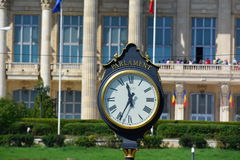 Parlament Clock. Romania, a trip, a clock in the background `house of the people` is the name of the Parliament, the beautiful huge building, probably second in Royalty Free Stock Photo