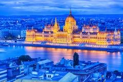 Parlament och flodstrand i den Budapest Ungern under blå timmesolnedgång Royaltyfria Bilder