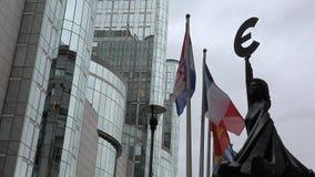 Parlamento Europeo en Bruselas, estatua euro del símbolo, banderas y el edificio moderno almacen de metraje de vídeo