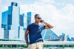 Parlando sul telefono cellulare, viaggiante a New York di estate Immagini Stock