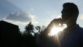 Parlando sul telefono, davanti al Sun durante il tramonto, siluetta Fotografia Stock Libera da Diritti