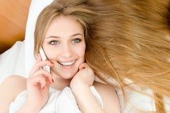 Parlando sulla ragazza bionda graziosa del telefono cellulare mobile con gli occhi azzurri, i chiodi rossi & i denti bianchi trov Immagine Stock