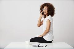 Parlare di risata della donna di affari africana sul telefono nel luogo di lavoro Immagini Stock