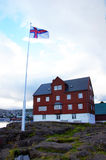 Parlement and flag of Torshavn  on Faroe Islands. Red parlement house of Tinganes on the Faroe Islands Stock Photos