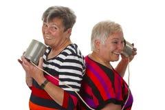 Parler aîné femelle avec le téléphone de bidon Images stock