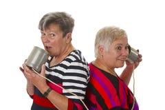 Parler aîné femelle avec le téléphone de bidon Photographie stock